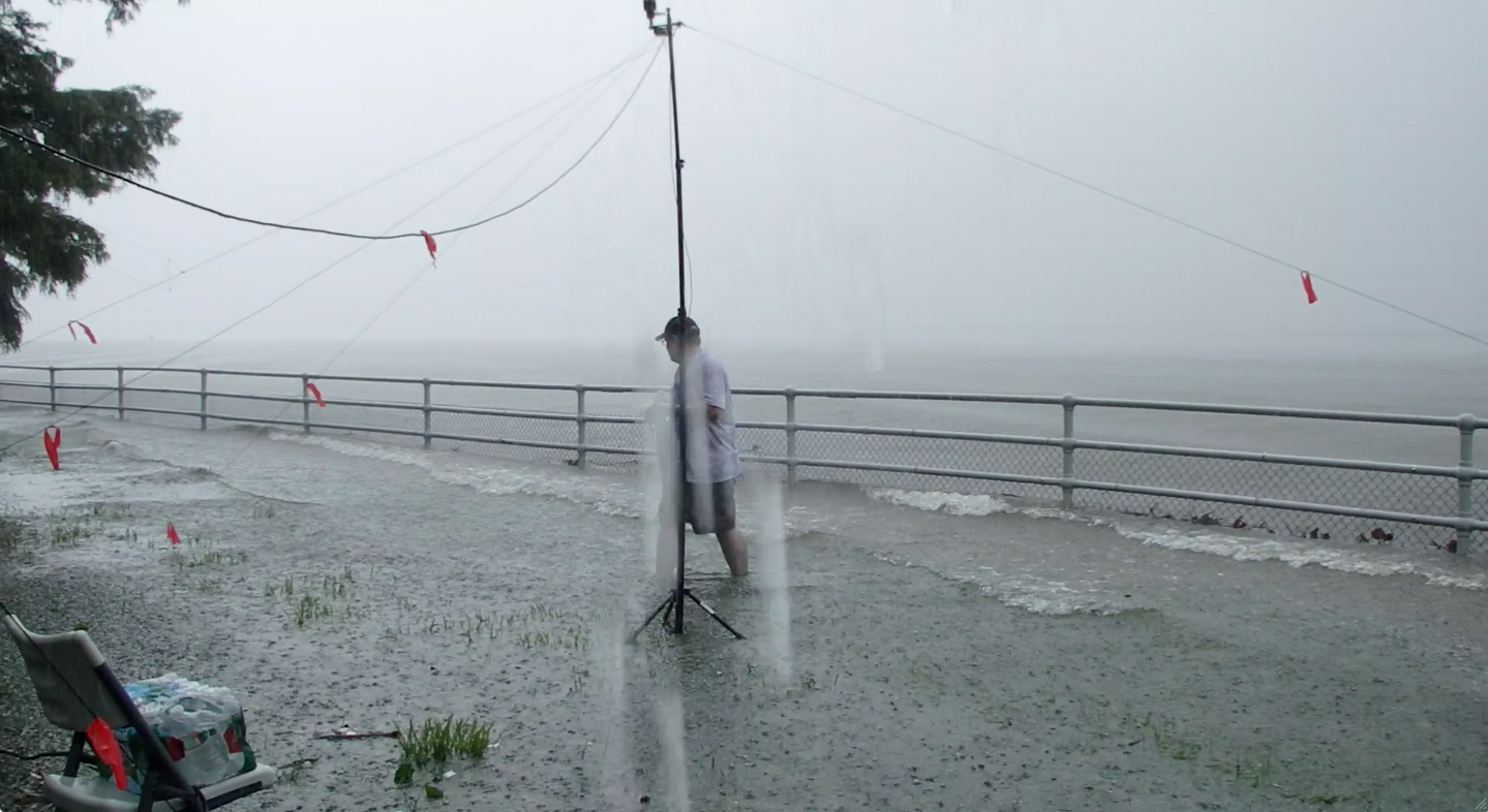 In rising waters, Darian (AB3WB) takes down the guy wires for his antenna.
